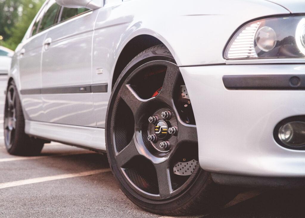 a white car with carbon fiber wheels