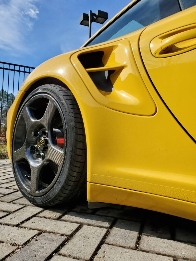 a yellow car with carbon fiber wheels